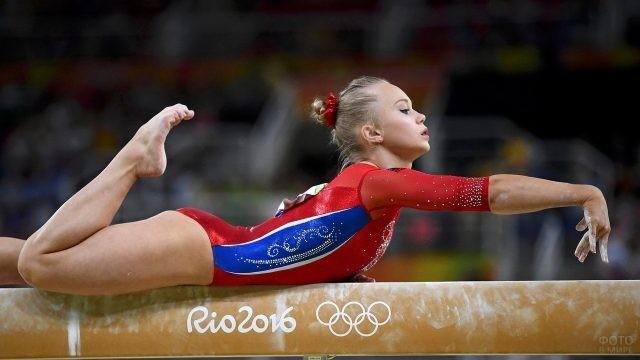 Гимнастка лежит на снаряде
