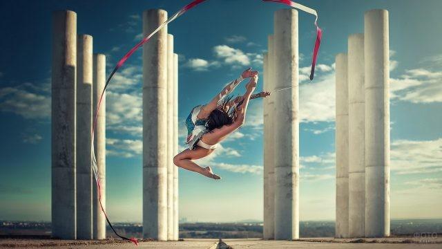 Прыжок гимнастки с лентой у колонн