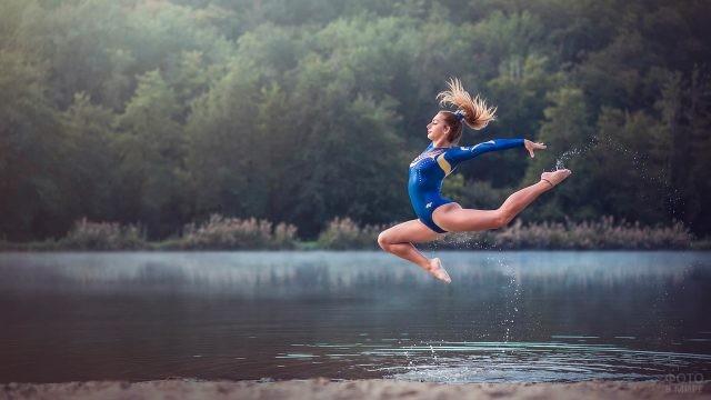 Русая девушка в прыжке над водоёмом