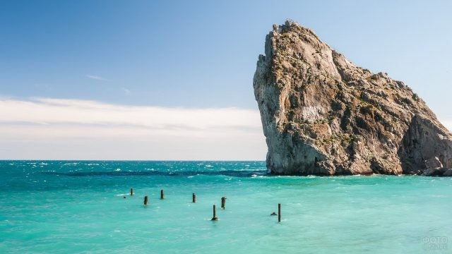 Скала в море у колышков для лодки