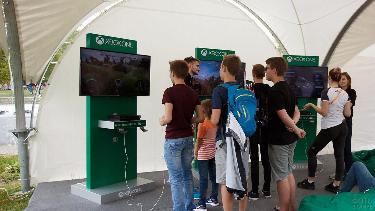 Посетители стенда с компьютерными симуляторами танкового боя в День танкиста