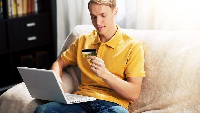 Юноша с банковской картой и ноутбуком проводит оплату через интернет