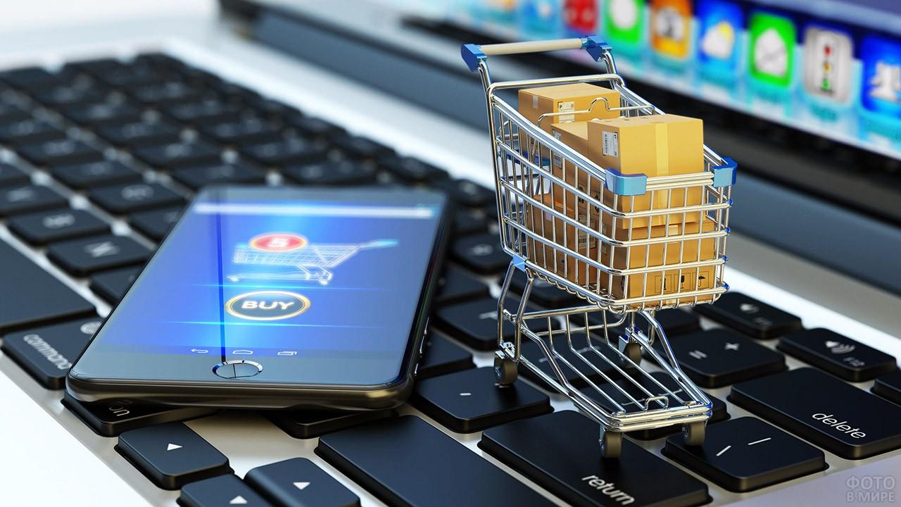 Маленькая тележка для покупок на клавиатуре и смартфон с интернет-магазином на экране