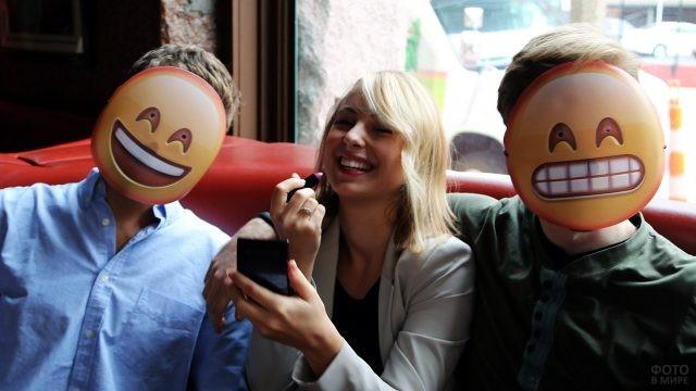 Смеющаяся девушка в компании парней с эмодзи-масками