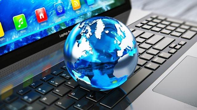 Стеклянный макет земного шара лежит на клавиатуре ноутбука