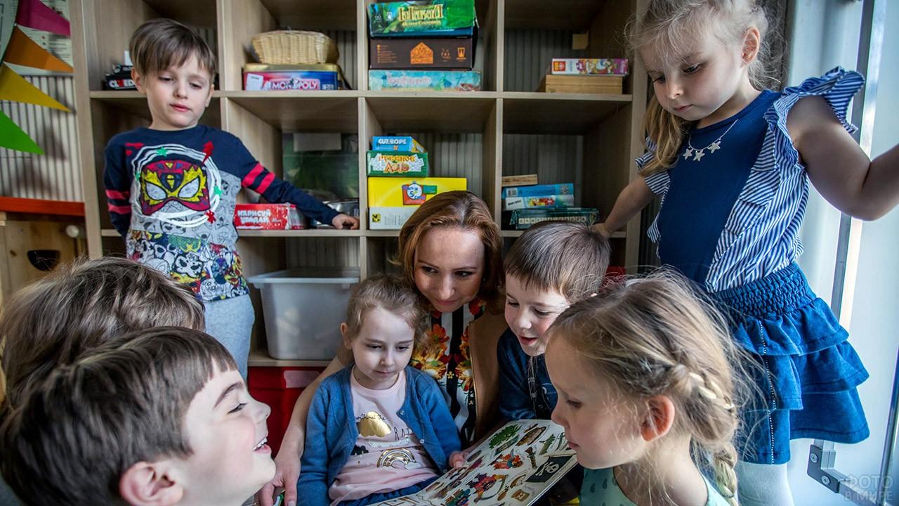 Дети с воспитательницей разглядывают книжку