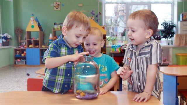 Мальчишки в детском саду разглядывают рыбку в банке