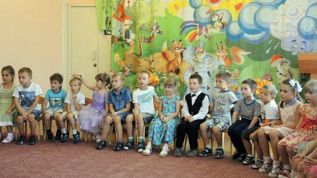 Малыши сидят кружком на утреннике в честь Дня воспитателя