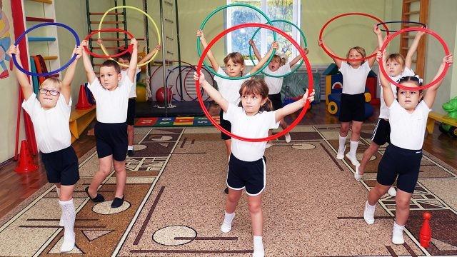 Малыши в детском саду делают гимнастику с обручами