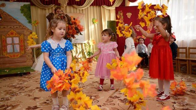Малышки с осенней листвой на утреннике в День воспитателя