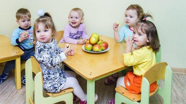 Симпатичные малыши в детском саду перед обедом