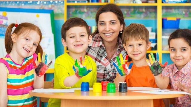 Воспитательница и малыши с ладошками раскрашенными гуашью