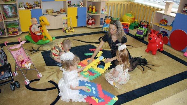 Воспитательница играет с детьми в группе детского сада