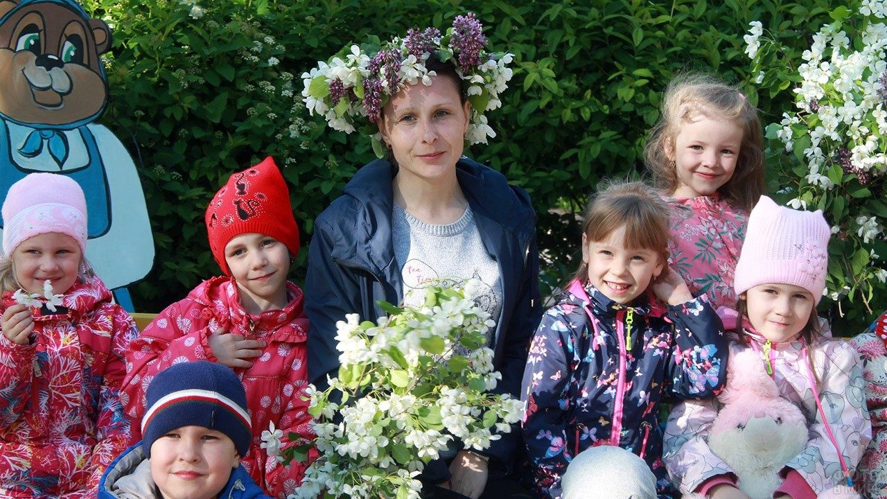 Воспитательница с детьми во дворе детского сада