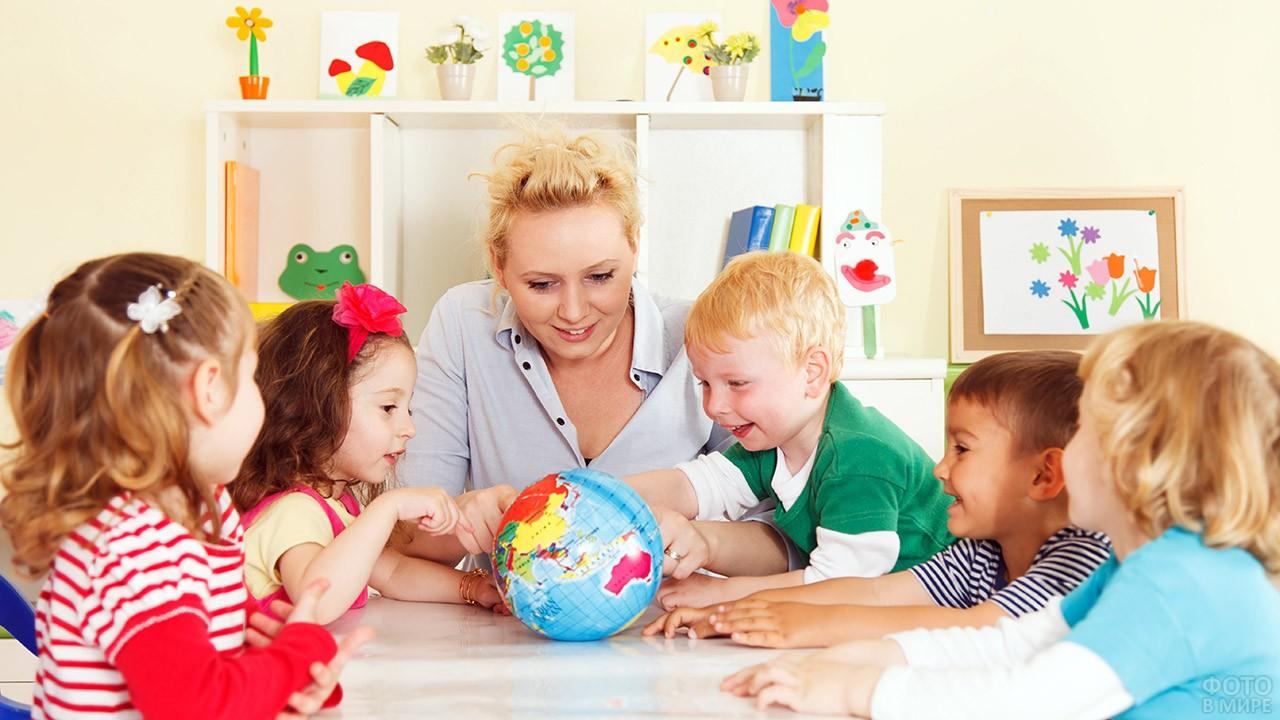 Воспитательница с малышами смотрят на глобус
