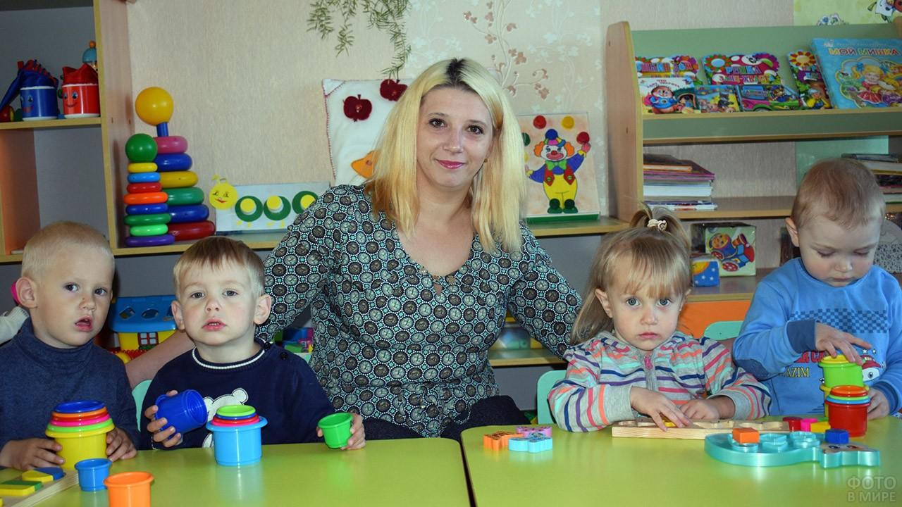 Воспитательница с малышами в игровом уголке детского сада