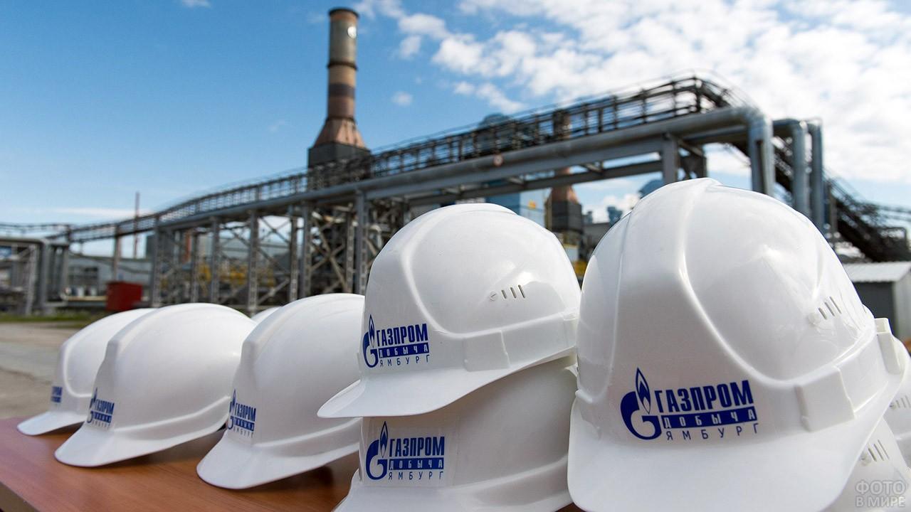 Каски с логотипом Газпрома на фоне газораспределительной станции