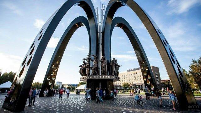 Люди гуляют у памятника нефтяникам в Сургуте