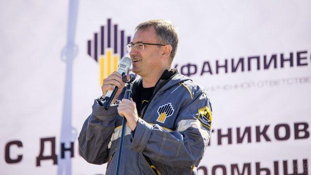 Сотрудник нефтяной компании в профессиональный праздник поздравляет со сцены своих коллег