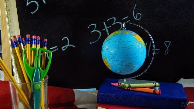 Глобус и книги с карандашами на фоне школьной доски