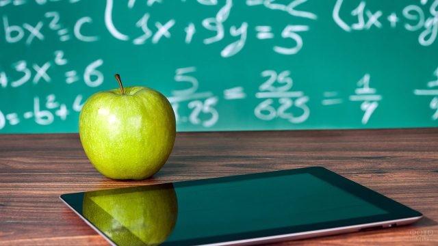 Яблоко и планшет на фоне исписанной доски