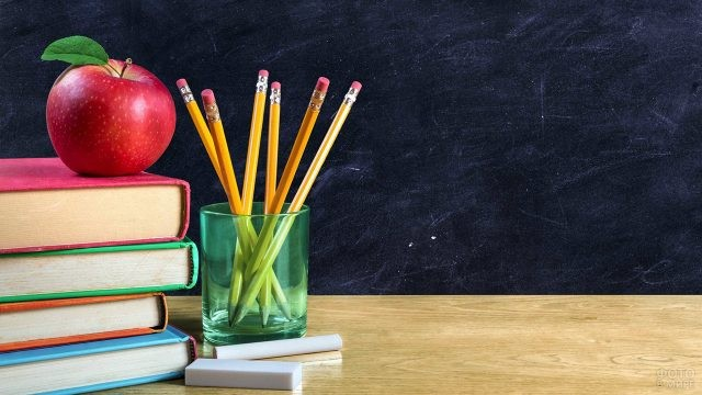 Яблоко на стопке книг и стакан с карандашами на фоне доски