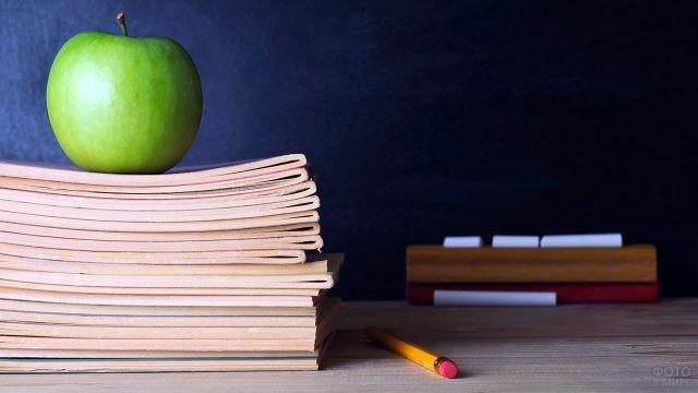 Яблоко на стопке тетрадей