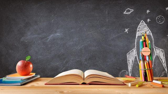 Яблоко, тетради, открытая книга, карандаши и рисунок ракеты на школьной доске