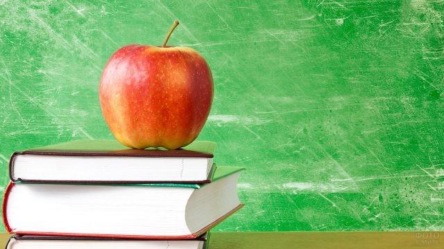 Красное яблоко на стопке книг на фоне зелёной доски