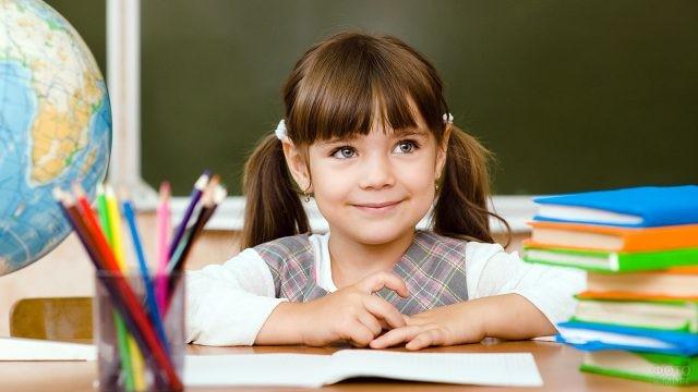Маленькая девочка за партой среди школьных принадлежностей