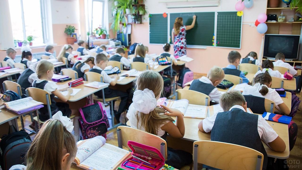 Нарядные школьники за партами и учитель у доски во время ...