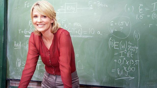 Школьная учительница у доски с задачами по физике