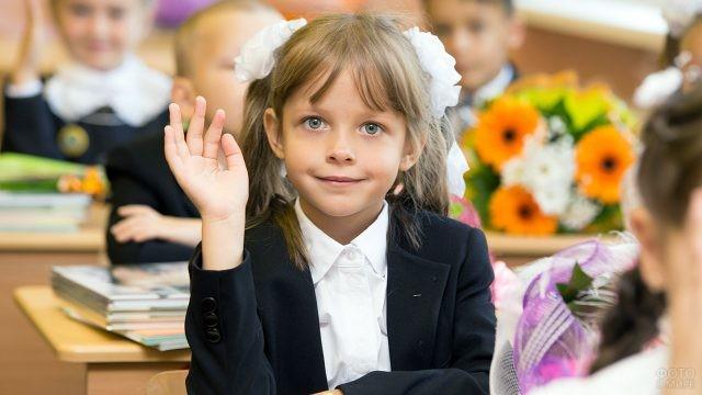 Школьница с белыми бантиками за партой тянет руку с ответом