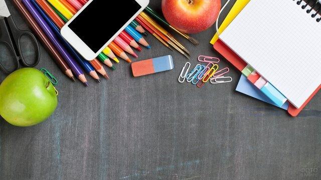 Школьные принадлежности и смартфон на грифельном фоне