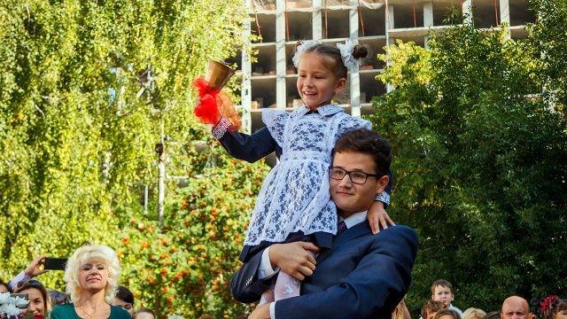 Старшеклассник держит на плече первоклассницу с колокольчиком 1 сентября