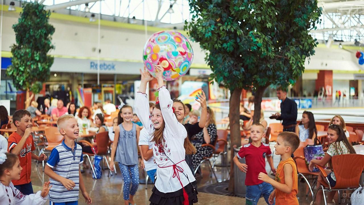 Дети играют в мяч в День знаний в фудкорте торгового центра