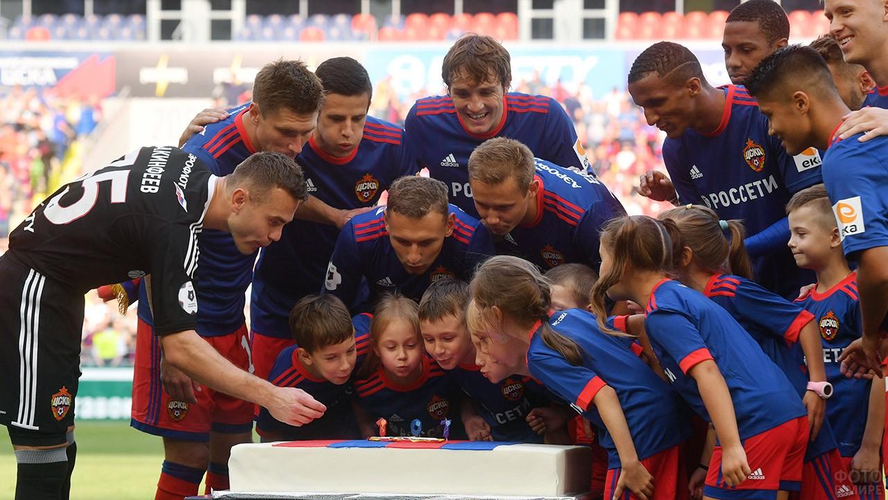 Школьники и футболисты ЦСКА задувают свечи на торте