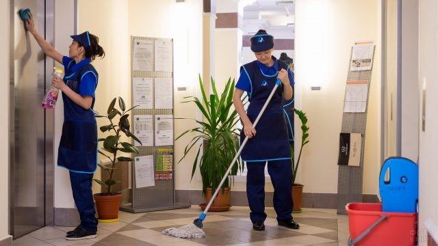 Азиатские уборщицы прибирают холл