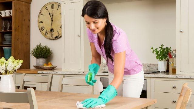 Брюнетка протирает кухонный стол