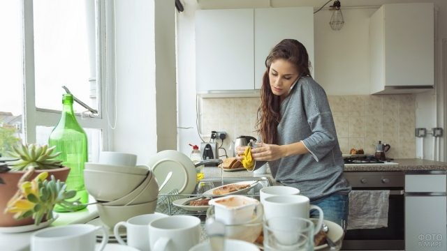 Девушка с телефоном моет посуду