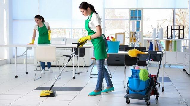 Девушки в фартуках убирают офис