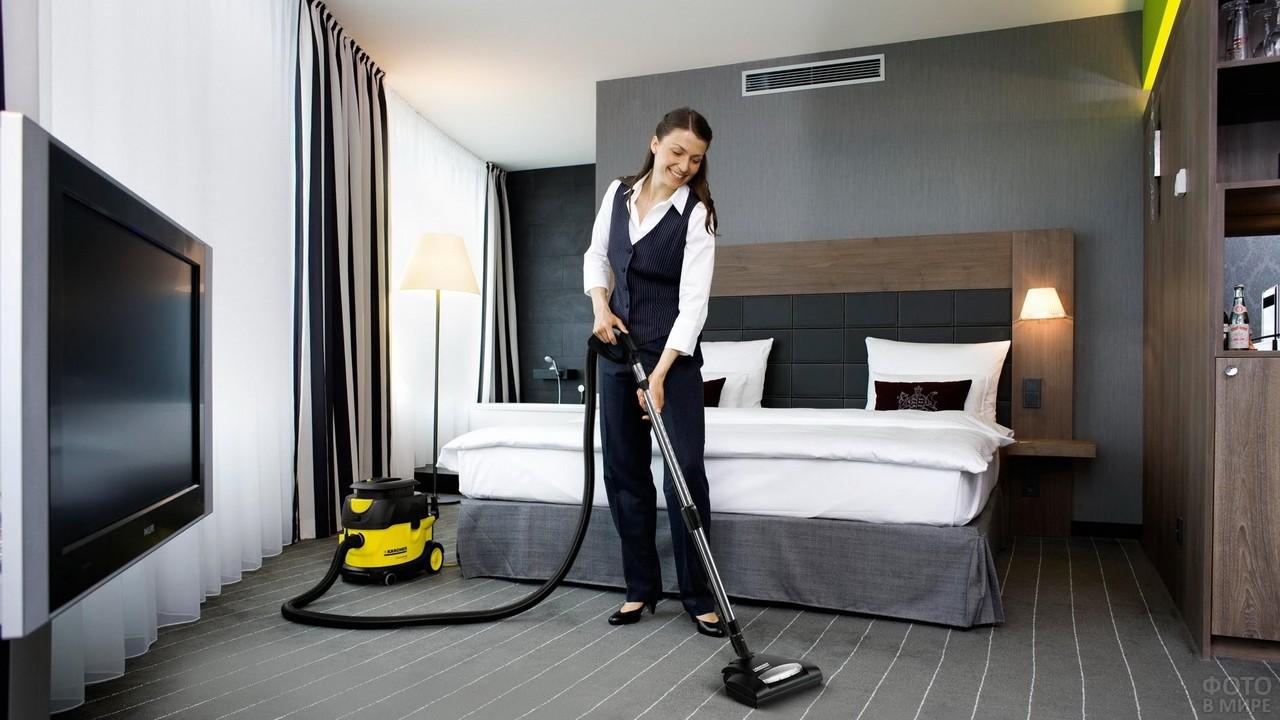 Горничная пылесосит пол в номере