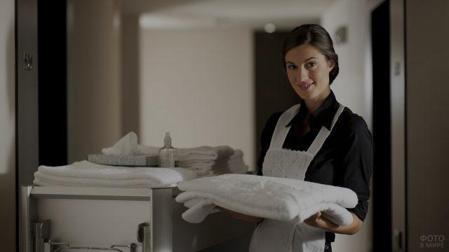 Горничная с полотенцем в коридоре