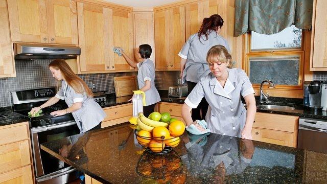 Команда уборщиц прибирает кухню