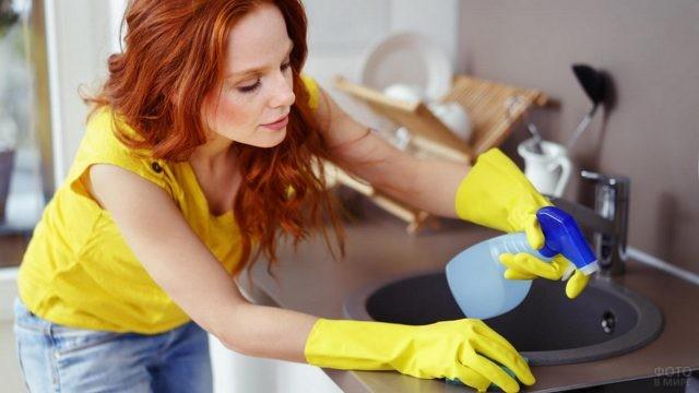 Рыжая уборщица чистит плиту