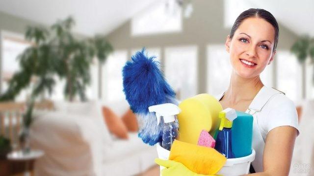 Уборщица держит ведро с инвентарём для уборки