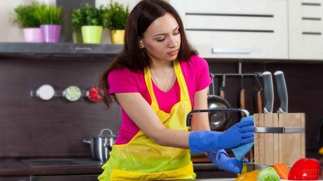 Уборщица моет кран на кухне