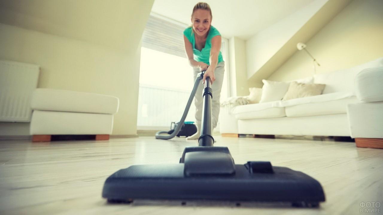 Женщина пылесосит светлую комнату