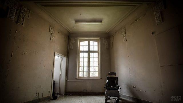 Инвалидное кресло в пустой комнате