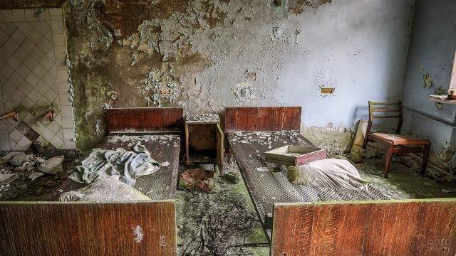 Пустые кровати в облупившейся комнате